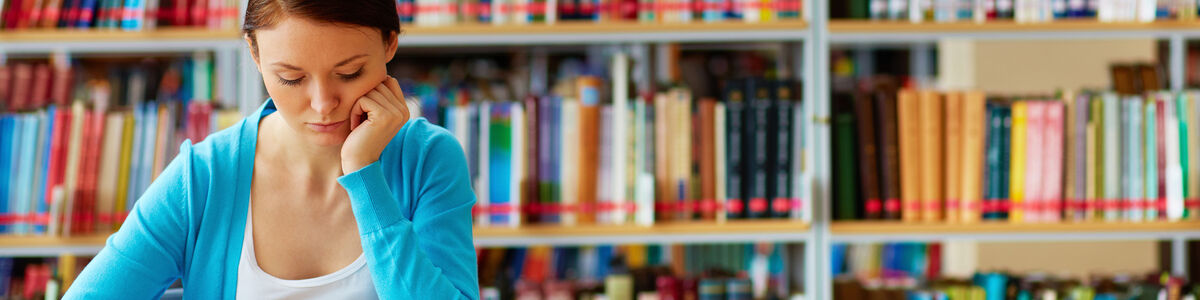 Pige læser på biblioteket