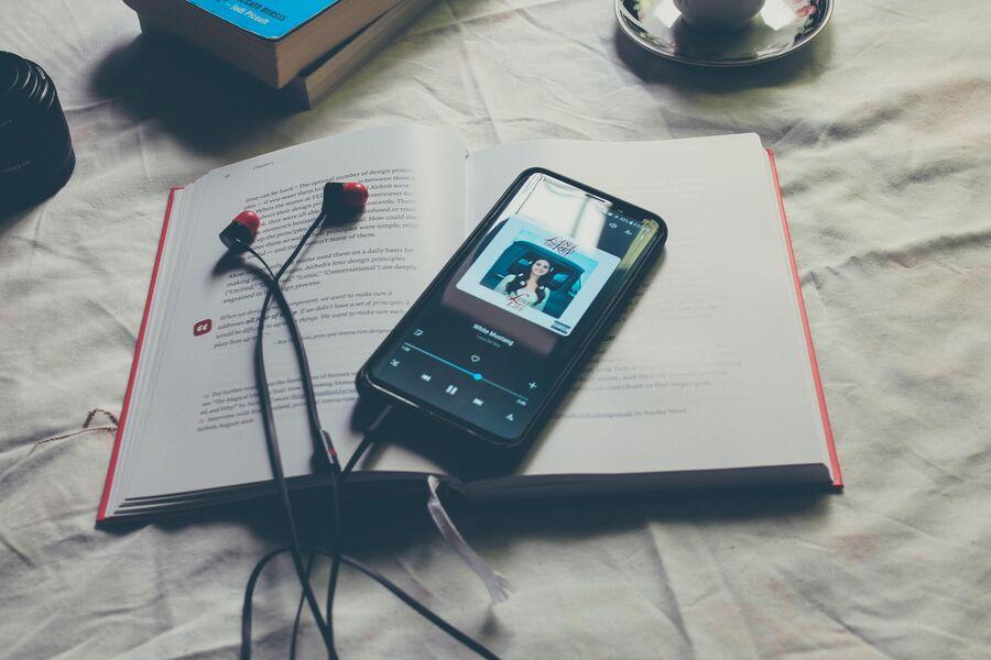 Smartphone med høretelefoner på bog