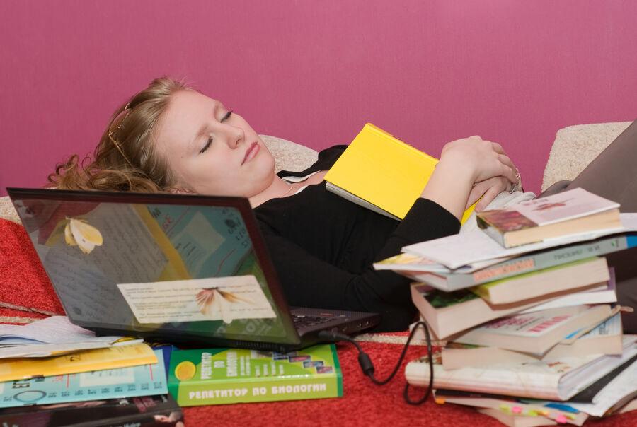 En person, der sover på og med bøger